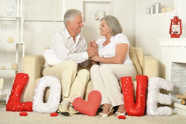 サイン愛とソファで家に座っている2人の高齢者
