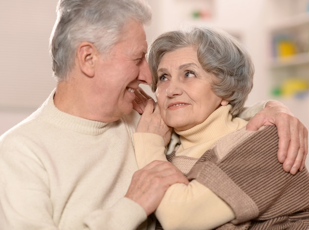 Two elderly people sitting at home on couch
