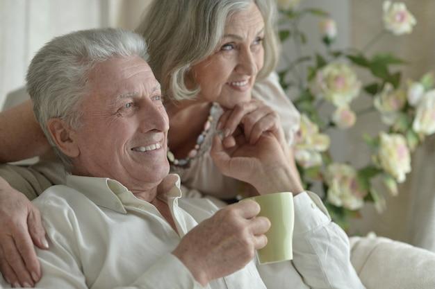 お茶とソファの近くに座っている2人の高齢者