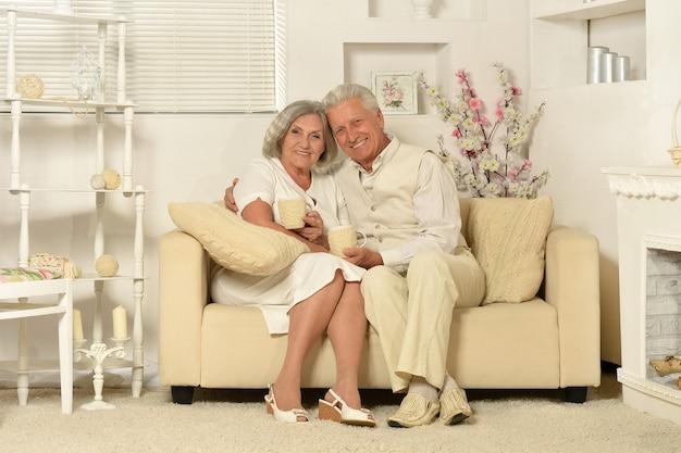 お茶とソファに座っている2人の高齢者