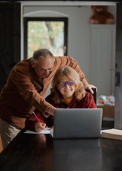 Two elderly people surfing internet on laptop computer at home. 4k video