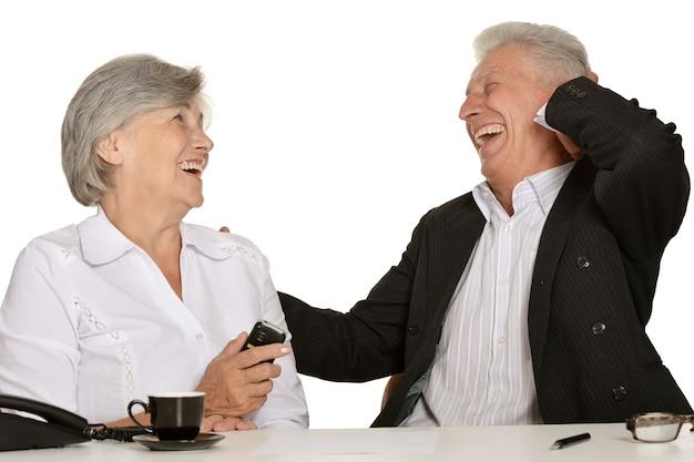 흰색 배경에서 노트북으로 작업하는 두 노인