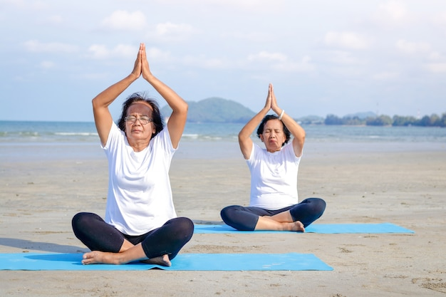 Two elderly women are exercising at the seaside beach, sitting and doing yoga.