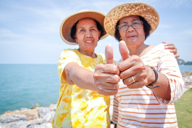 Two elderly women are friends visiting the sea in happy retirement.