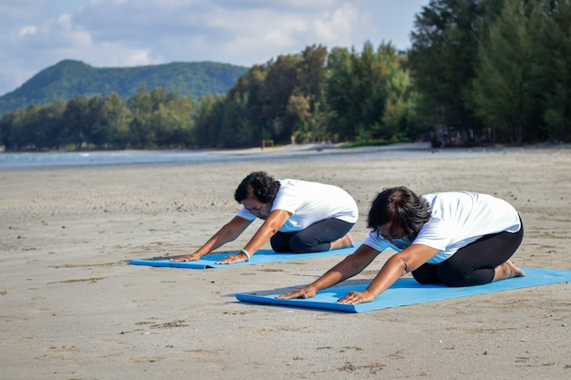 Two elderly women exercising at the beach are doing yoga.