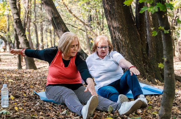 Two elderly women friends workout in nature sitting on mat,practice yoga.seniors stretching outdoors persistence to lose overweight.never to late to start exercise