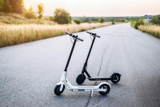 Два электрических скутера, черно-белые, стоят посреди дороги во время заката в сельской местности.