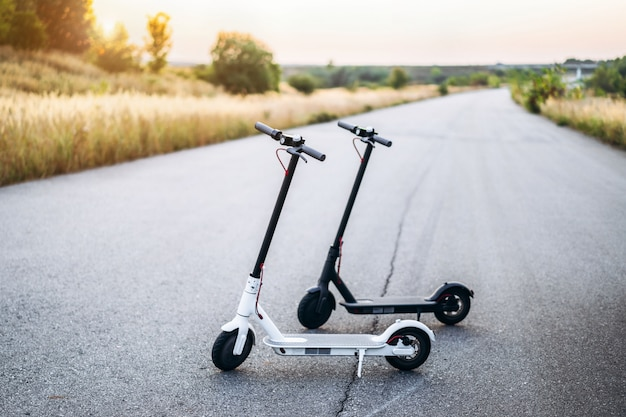 Two electric scooters, black and white, stand in the middle of the road at sunset time in the countryside.