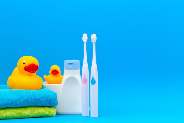 Two electric toothbrushes and accessories for bath on blue background.