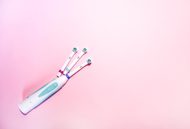 Две электрические зубные щетки на мягком светло-розовом фоне.