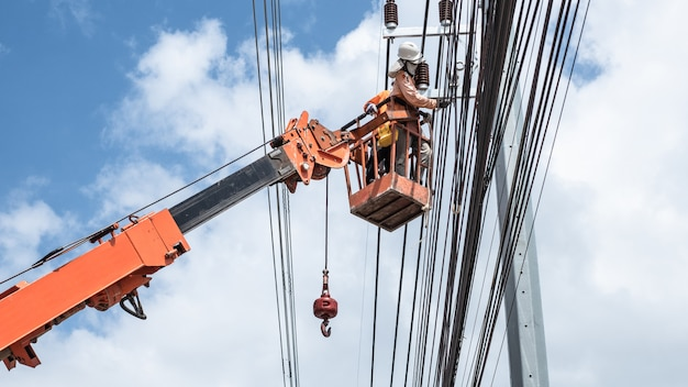 Two electrician workers are climbing on the electric poles to install and repair power lines.