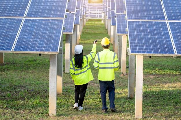 반사 조끼와 안전모를 입은 두 명의 전기 기술자가 태양 전지판에서 일하고 새로운 태양 전지판 설치에 대해 이야기하고 있습니다.