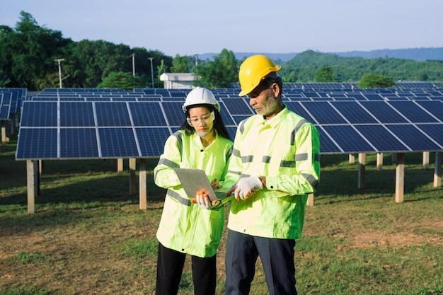 태양 전지판에서 일하는 반사 조끼와 안전모에 두 명의 전기 기술자.