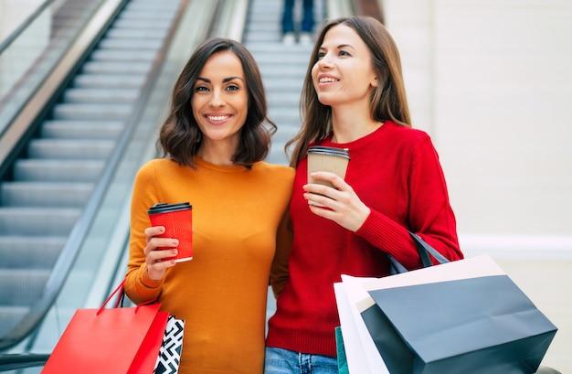 ブラックフライデーセール中にショッピングバッグを持った2人のエレガントでスタイリッシュな美しい若い女性がモールを歩いています
