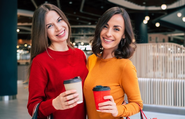 Две элегантные и стильные красивые молодые женщины с хозяйственными сумками гуляют по торговому центру во время распродажи в черную пятницу
