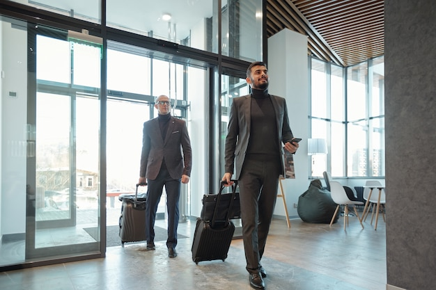 Two elegant business travelers pulling suitcases while entering hotel lounge after arrival in foreign country