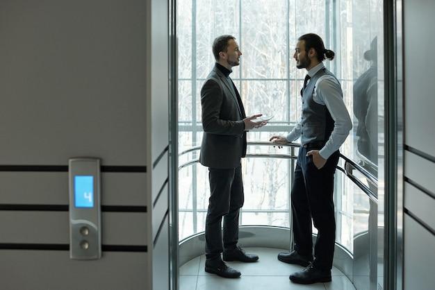 Два элегантных бизнесмена обсуждают рабочие точки или условия соглашения в лифте крупного бизнес-центра