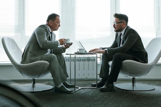 Два элегантных бизнесмена в костюмах сидят в креслах у большого окна офиса и обсуждают условия контракта или новые стратегии