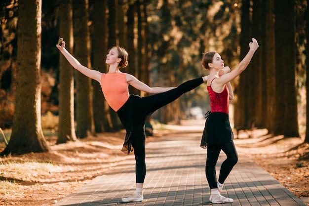 재미있는 포즈에 서있는 동안 화창한 공원에서 selfie를 만드는 두 명의 우아한 여성 발레 댄서.