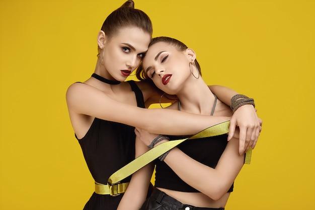 Two elegant glamor hipster twin girls in fashion black dresses