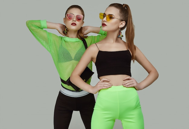 Two elegant glamor hipster twin girls in fashion neon green dresses