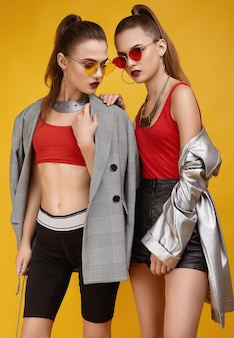 Two elegant glamor hipster twin girls in fashion red top, black shorts
