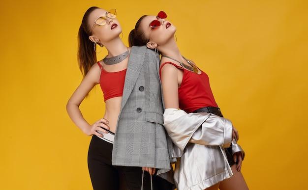 Две элегантные гламурные хипстерские девушки-близнецы в моде красный топ, черные шорты