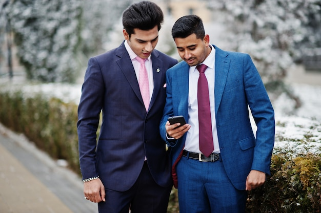 Two elegant indian fashionable mans model on suit posed at winter day looking at phone.