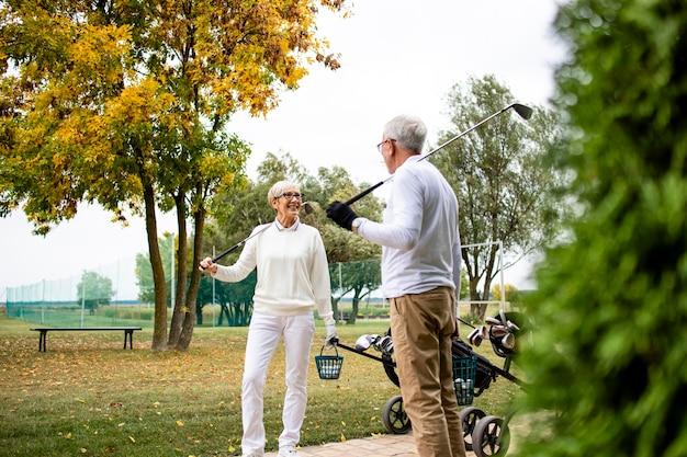 Два элегантных пожилых игрока в гольф вместе играют в гольф и проводят свободное время на пенсии.