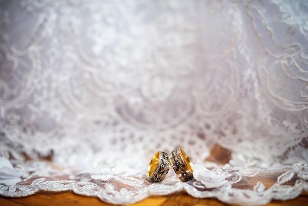 Two elegant wedding rings on a white dress