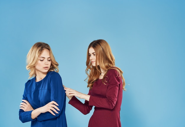 Two elegant women best friends lifestyle together blue background