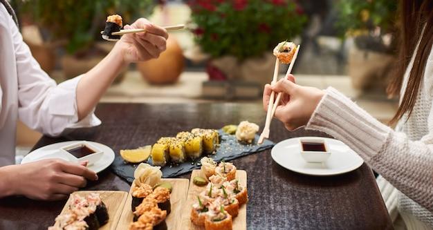 Two elegant women eating sushi set with wasabi and ginger.