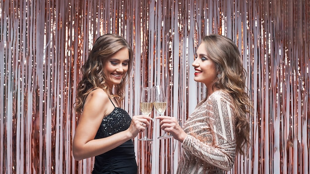 Two elegant women friends in evening dresses talking and drinking champagne.