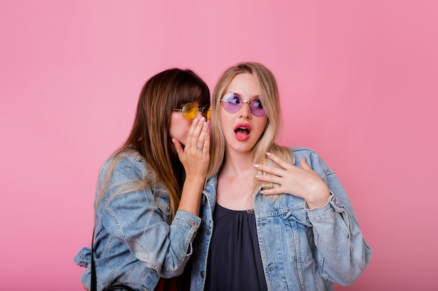 Due donne emozionali spettegolano sulla parete rosa