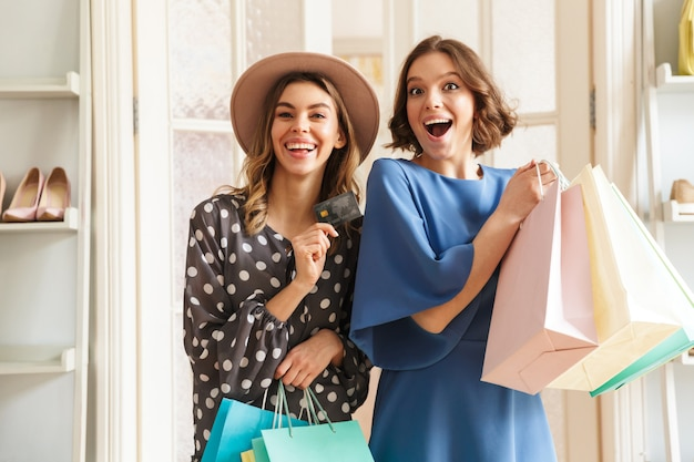 Two emotional young women shopaholics with shopping bags and credit card.