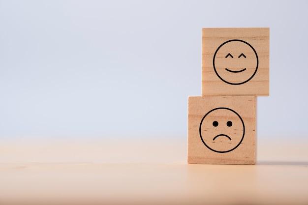 Две эмоции счастливого и грустного, которые печатают экран на деревянном кубике опрос клиентов и концепция обратной связи.