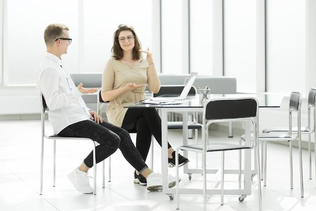 オフィスの机に座って新しいアイデアについて話し合う2人の従業員