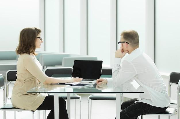 オフィスデスクに座っている2人の従業員