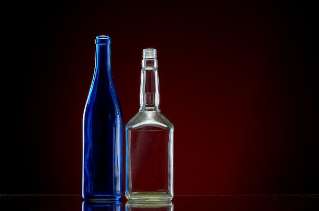 Two empty alcohol bottles on red
