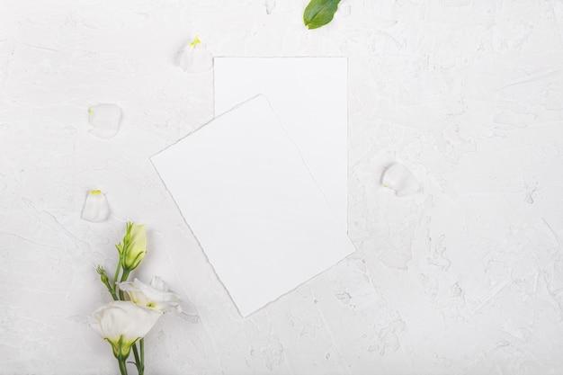 咲く白いトルコギキョウの花と2つの空のカードモックアップ