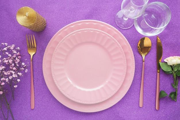 Две пустые керамические тарелки на блестящем фиолетовом