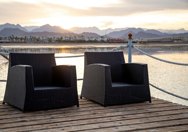 Two empty chairs on a wooden pier overlooking the mountains in the sunset light.