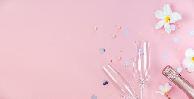 Two empty champagne glasses and bottle of champagne with white frangipani flowers and small heart decoration on pink background, copy space