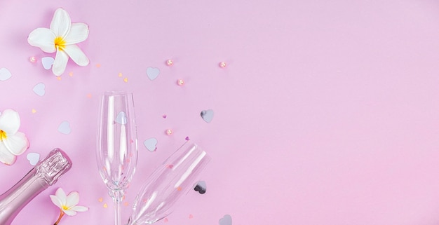 Two empty champagne glasses and bottle of champagne with white frangipani flowers and small heart decoration on pink background