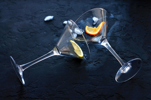 Two empty cocktail glasses will fall overturned out of them leaked liquid and ice next to pieces of fruit