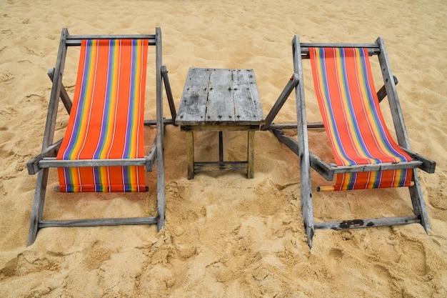 모래 해변에 두 개의 빈 다채로운 캔버스 라운지 슬링 의자와 나무 테이블