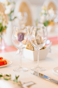Two empty glass glasses in the wedding decor on a festive banquet table