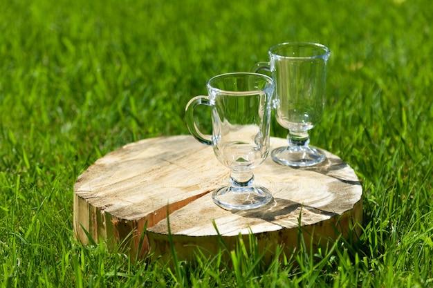 ハンドル付きの2つの空のガラスグラスは、晴れた夏の日に緑の芝生のひびの入った木製のスタンドの上に立っています。