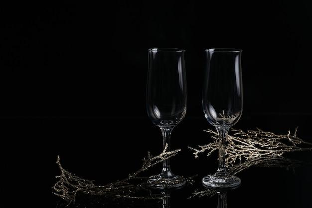 샴페인과 크리스마스 또는 새 해 장식 검정색 배경에 두 개의 빈 잔. 낭만적 인 저녁 식사. 겨울 휴가 개념.