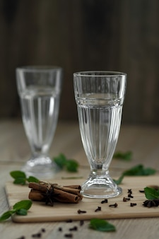 Two empty glasses on a wooden platform with ingredients for making a hot vitamin drink